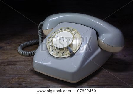 Retro Rotary Telephone Of Gray Plastic With Rotary Dial On A Dark Wooden Table