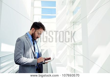 Skilled business man dressed in elegant corporate clothes work on digital tablet