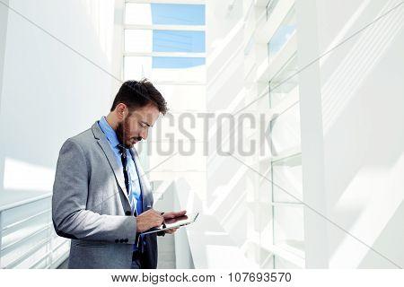Skilled business man dressed in elegant corporate clothes work on digital tablet
