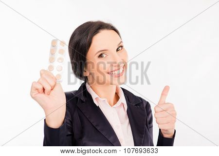Happy Young Businesswoman Holding A Pill For A Headache And Showing Thumbs Up