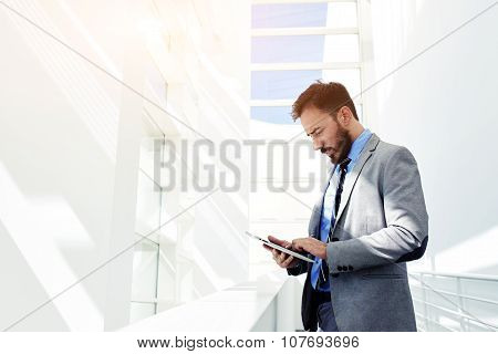 Young prosperous business man dressed in suit work on digital tablet during break