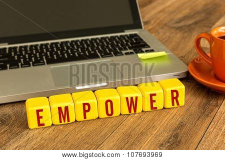Empower written on a wooden cube in a office desk