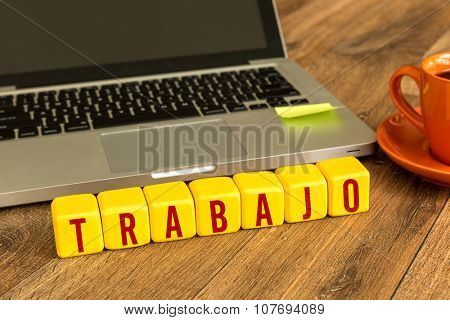 Work (in Spanish) written on a wooden cube in a office desk