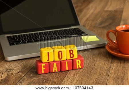 Job Fair written on a wooden cube in a office desk