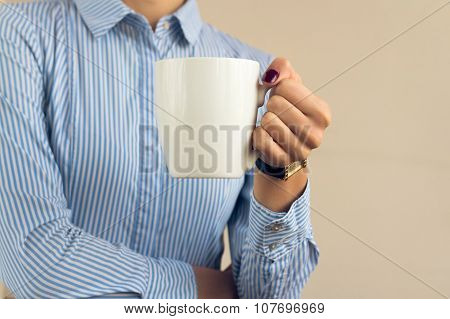 Woman With A Burgundy Manicure In A Blue Striped Shirt Holds A White Cup