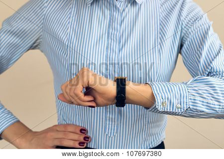Woman With A Burgundy Manicure In A Blue Striped Shirt Looking The Time On Hand Watch Closeup