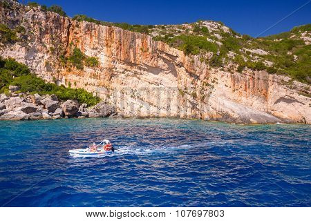 ZAKYNTHOS, GREECE - AUG 24, 2015: Boats with tourists at the Blue caves of Zakynthos island, Greece. Sunrays reflect through blue sea water from white limestones creating visual lighting effects.