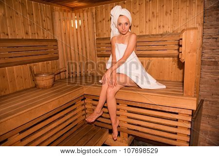 Pretty Girl In Towel Sitting On The Bench In Sauna