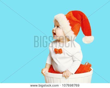 Christmas And People Concept - Cheerful Baby In Santa Red Hat Looking Up
