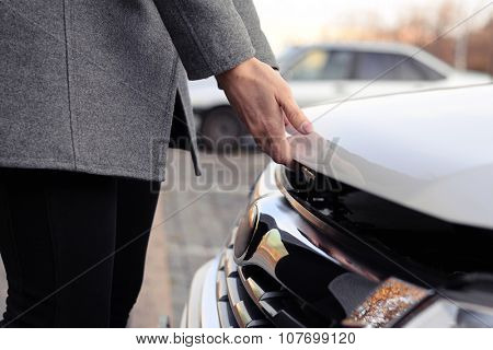 closeup photo of womans hands open the bonnet at outdoor