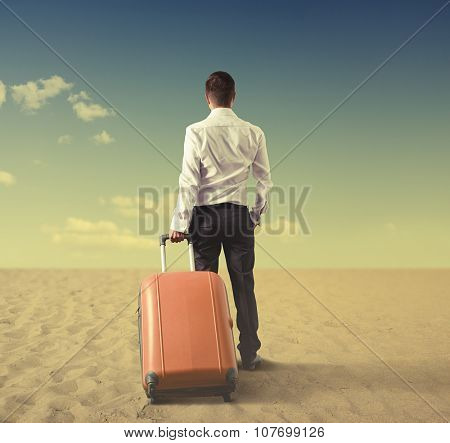 back view of businessman with bag standing in desert and looking at the distance