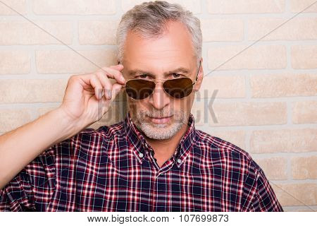 Portrait Of Handsome Old Man Holding Sunglasses