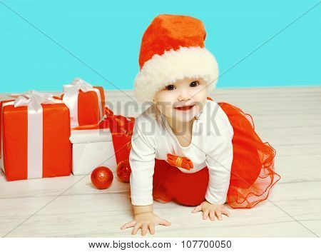 Christmas And People Concept - Smiling Child In Santa Red Hat With Boxes Gifts Crawls On Floor