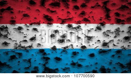 Flag of Luxembourg painted on wall with bullet holes