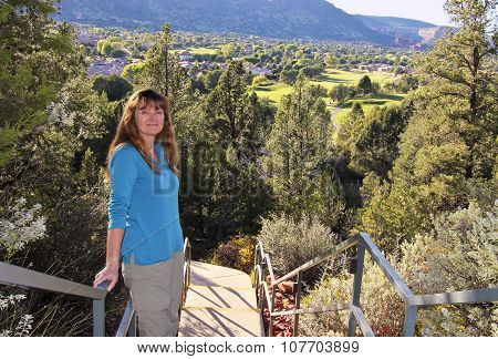 An Attractive Woman On A Stairway Above A Golf Course
