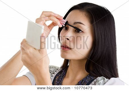 Young Woman Putting On Black Mascara