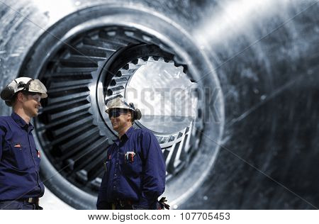 two metal workers, mechanics in front of large cogwheels axle, symbolic with steel industry