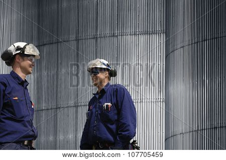 two workers, engineers and stainless-steel wall