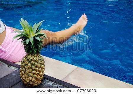 Close-up Of Pineapple And Female Leg In The Swimming Pool