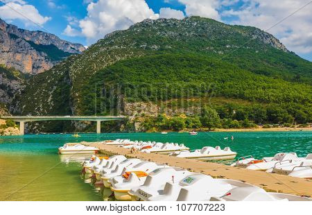 Gorgeous round wooded mountain at the entrance to Verdon Gorge. Wooden pier with white catamaran