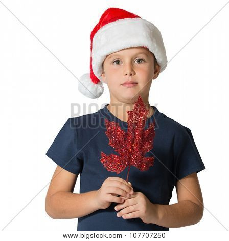 Boy in the red hat of Santa Claus posing with decoration for Christmas tree - maple leaf.  Photographed on a white background