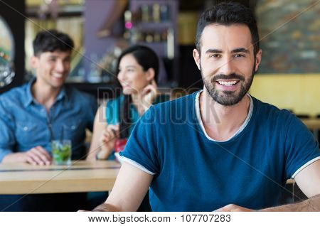 Closeup shot of young man looking at camera. Handsome guy smiling at coffee bar. Portrait of happy young man in casual sitting at a table in a bar.