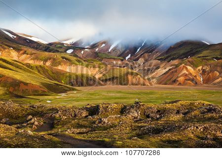 Pink dawn in the Arctic. Striped mountains of rhyolite covered sunshine.  National Park Landmannalaugar, Iceland