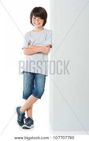 Smiling little boy posing against grey wall isolated on white background. Young boy leaning against a grey sign and looking at camera with arms crossed.
