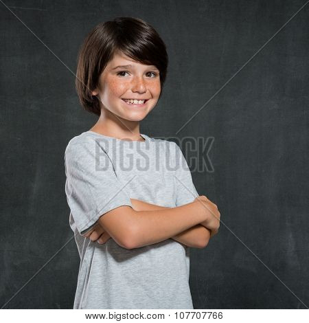 Closeup shot of little boy standing with armcrossed isolated on blackboard. Portrait of kid smiling and looking at camera. Pride little boy in casual clothes.