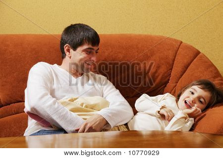 Father Sitting With Daughter On Sofa