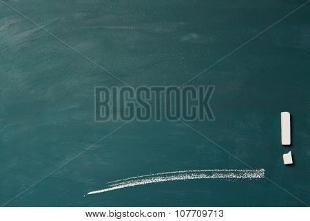 Empty green chalkboard with line and broken chalk as exclamation point