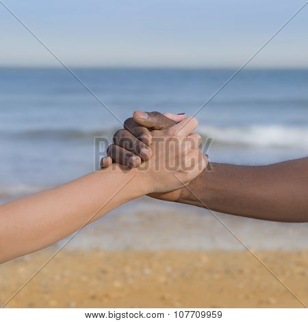 Man and woman holding each other's hand (symbol of love and diversity)