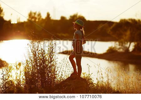 Little Girl In Hat Stands On The River Bank At Sunset