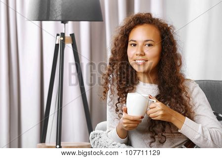 Young beautiful woman drinking coffee on sofa in the room