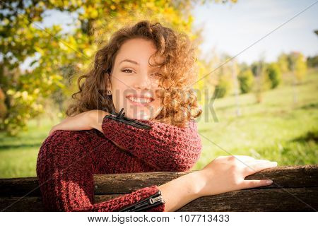 Beautiful young woman with curly hair sitting on the wooden bench in the park at autumn