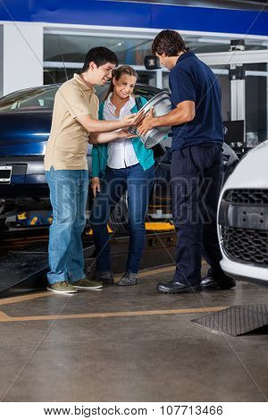 Couple and technician discussing over metallic alloy at auto repair shop
