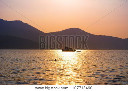 Small boat sails over the sea with sun reflection on surface at sunset