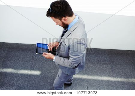 Young men professional banker in suit using touch pad during work break