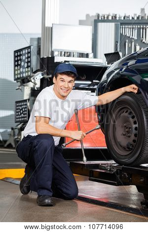 Portrait of smiling male mechanic holding rim wrench while kneeling by car at garage
