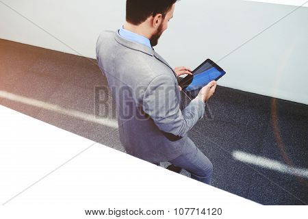 Young confident man economist holding digital tablet with copy space screen for your text