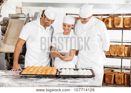 Smiling male and female Baker's using digital tablet while preparing breads in bakery