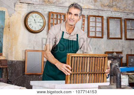 Mature male worker dipping mold in pulp and water while looking away at paper factory