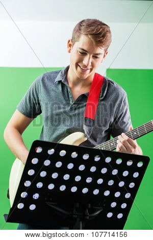 Smiling young male guitarist performing while looking at musical notes in recording studio