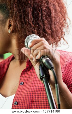 Midsection of female singer holding microphone in recording studio