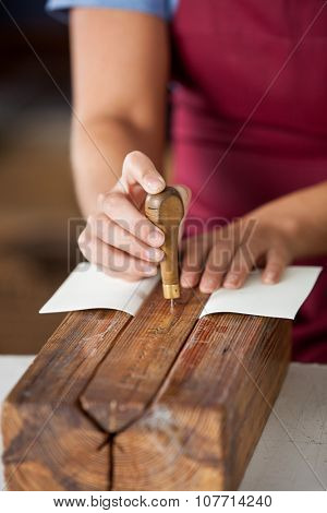 Midsection of female worker using needle to make holes on book binding
