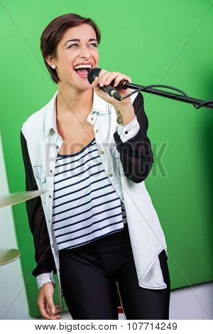 Happy young woman singing while holding microphone in recording studio