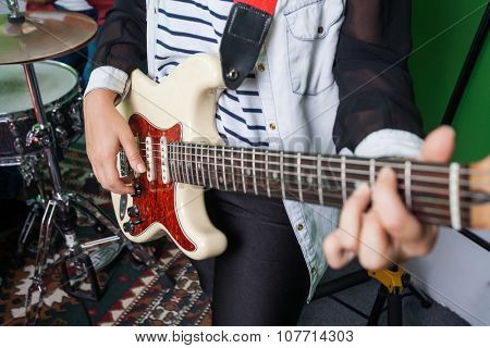 Midsection of female guitarist performing in recording studio