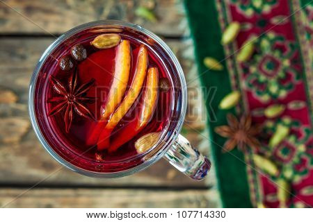 Mulled wine with orange, cinnamon, anise and other spices in glass cup. Traditional winter season ch