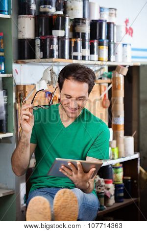 Smiling male worker holding eyeglasses while using digital tablet in paper factory