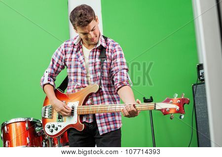 Handsome male professional playing electric guitar in recording studio